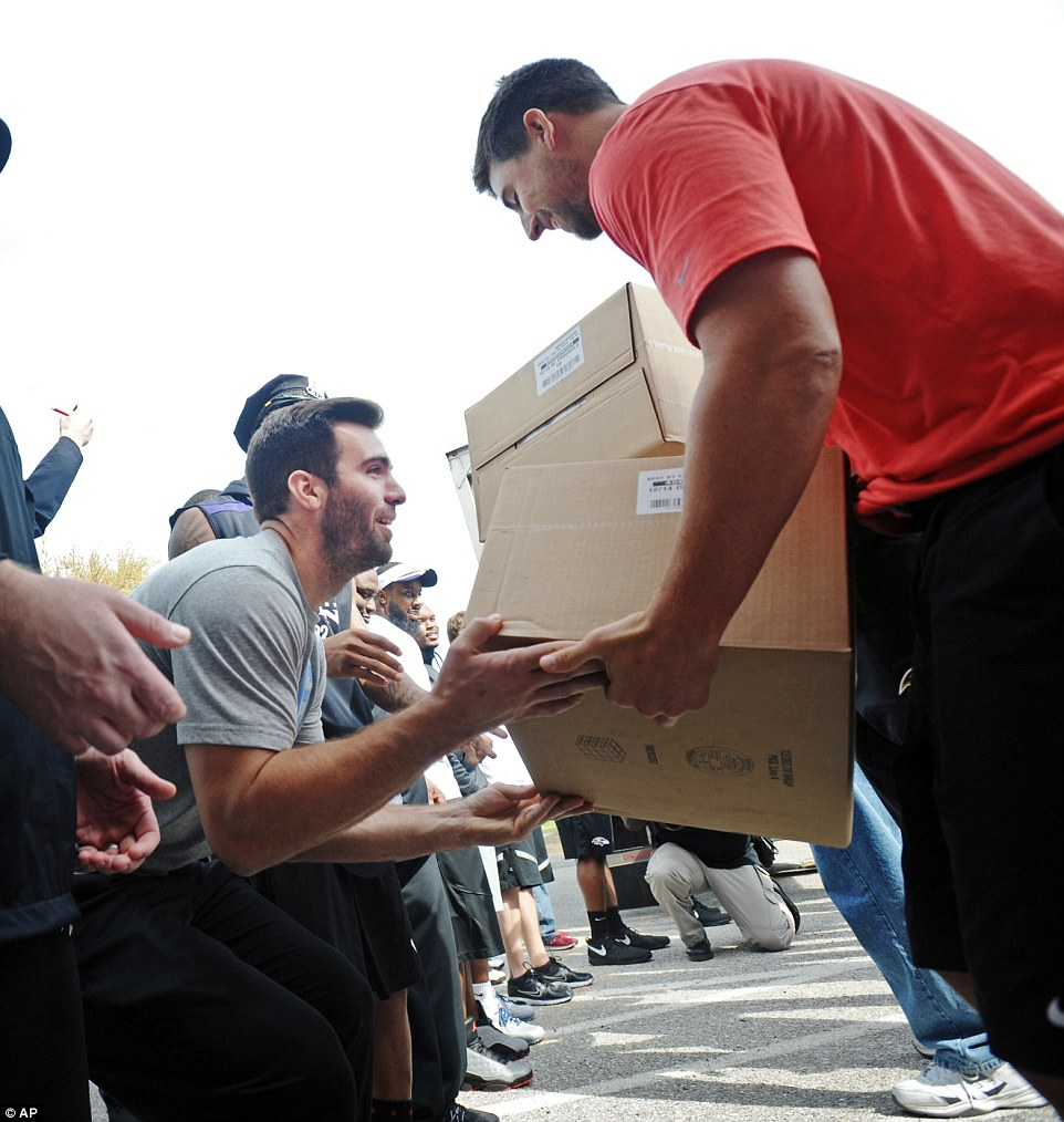 baltimore ravens tight end dennis pitta right takes a box of food