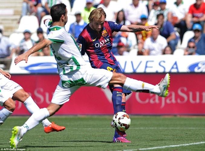 Barcelona's attacking midfielder Ivan Rakitic (right) sees his shot closed down by Cordoba'sInigo Lopez (left) on Saturday