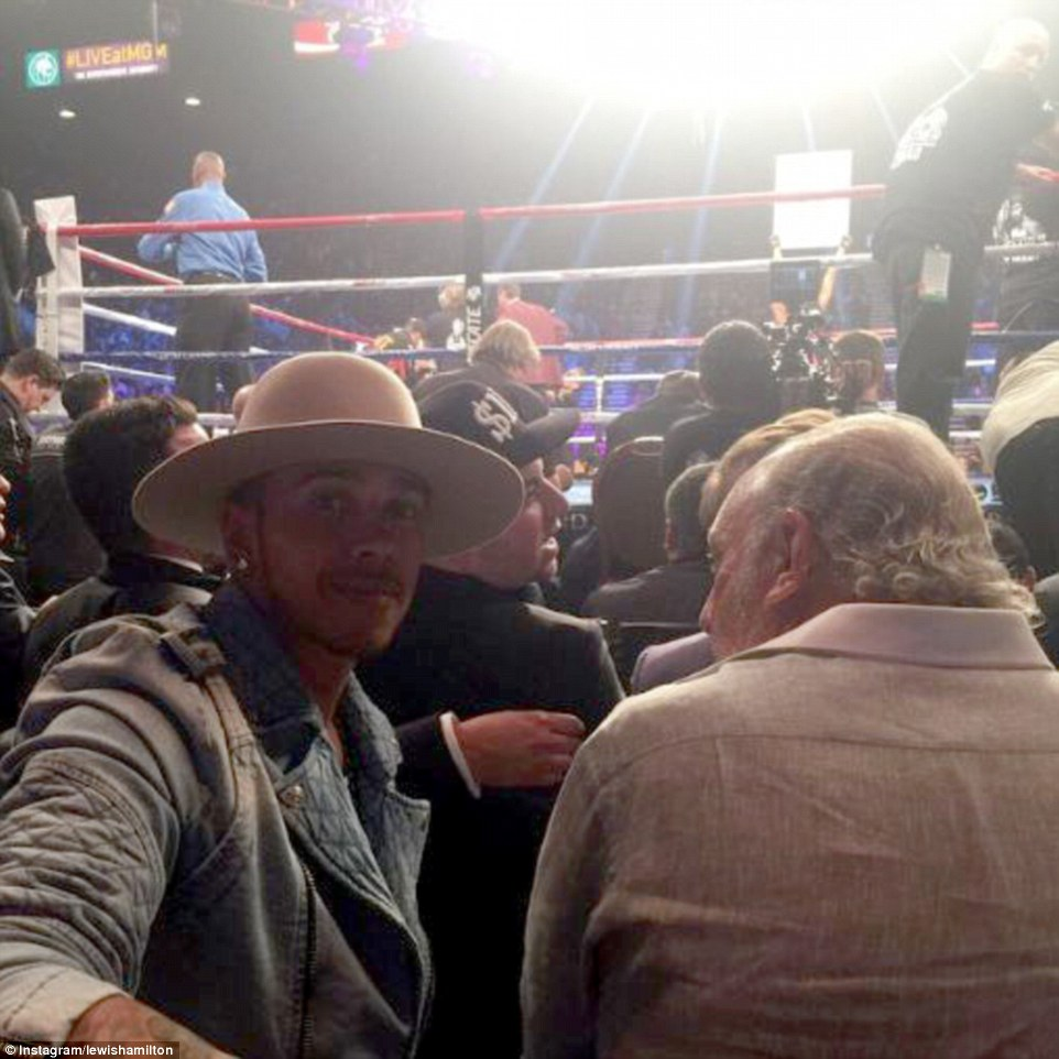 Formula One star Lewis Hamilton watches the fight from ringside with businessman Sir Phillip Green