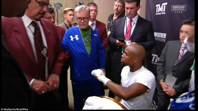 Pacquiao's coach Freddie Roach (centre) kept a close eye as Mayweather had his hands wrapped ahead of the fight