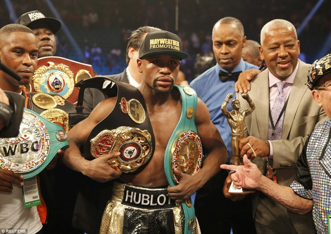 Mayweather poses with his welterweight belts - the one he was awarded for this latest victory is worth $1m