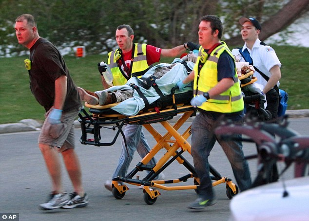 Rushed to hospital: A man is carried away on a stretcher. Three men, including the gunman, died
