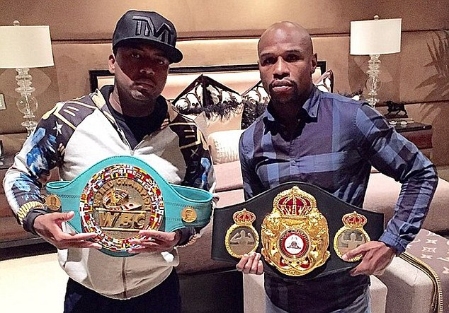 Floyd Mayweather poses with the WBO welterweight belt as P-Reala holds the WBC version