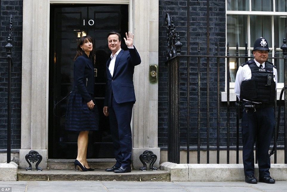 David Cameron gives a triumphant wave on the steps of Number 10 with his wife Samantha Cameron at his side as the results continue to fall in the Tories' favour