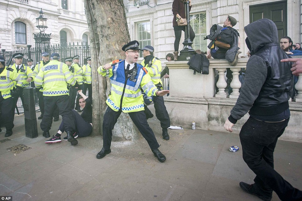 Police officers deployed their extendable batons in an effort to prevent the protesters, some of whom were masked, from Downing Street