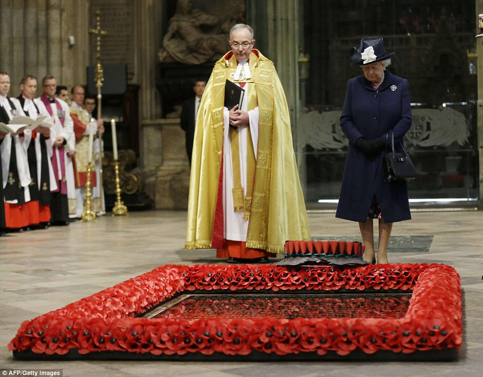 The Queen looks down after a wreath was laid on her behalf at the grave of the Unknown Warrior with the Dean of Westminster John Hall at the start of a service of thanksgiving to mark the 70th anniversary of VE Day
