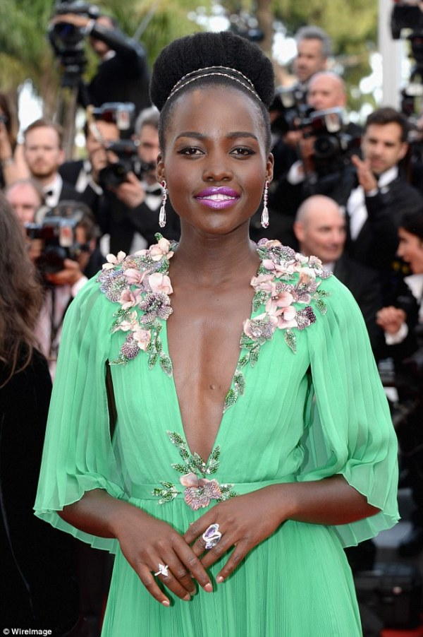 Bright thing: The 32-year-old wowed in a plunging green dress by Gucci for the occasion with contrasting purple lipstick