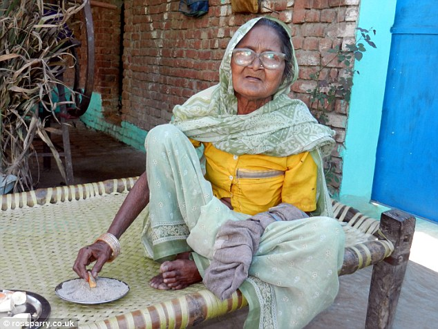 Although Mrs Devi, perched on a wicker bench (above), has been eating the substance for decades, she doesn't class sand as 'food'