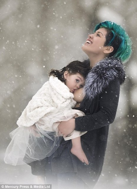 A mother breastfeeds in the snow