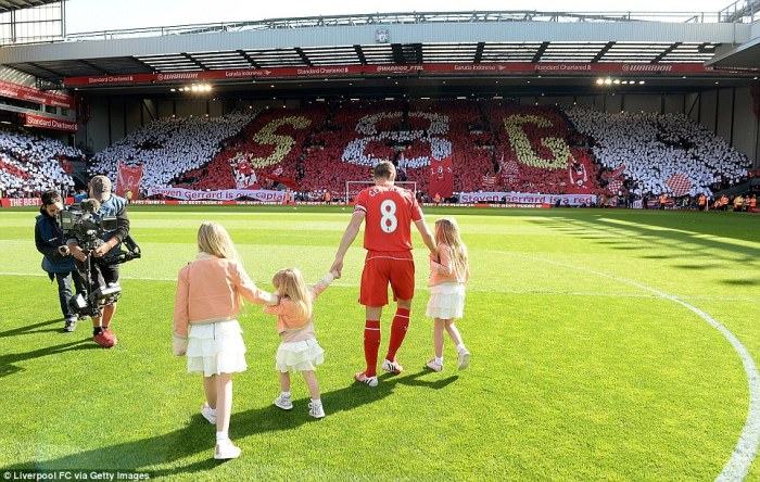 Tribute: Gerrard, with his three daughters, is faced by the Kop, a sea of red and white, with their 'S8G' tribute to their inspirational captain