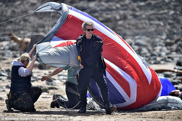 Action! Peter Capaldi hit Barry Island beach on Monday with a patriotic parachute to shoot scenes for the ninth series of Doctor Who