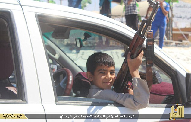 Innocence lost: ISIS has released pictures showing its militants - and young followers (pictured) - celebrating the capture of Ramadi as Shi'ite militias prepare a counter-offensive to retake the city