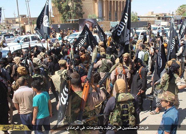 Celebration: Hundreds of ISIS fighters carrying the notorious black flag of jihadi groups celebrate in the blood-stained streets of Ramadi (pictured)