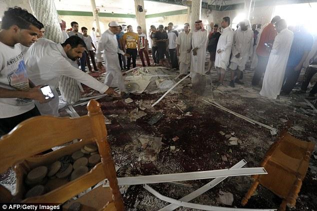 Horror: Saudi men gather around debris following a blast inside a mosque, in the mainly Shi'ite Saudi Gulf coastal town of Qatif, 400 kms east of Riyadh