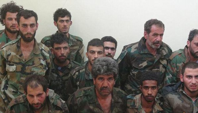 Distressing: The photographs show 20 Syrian soldiers, dressed in full uniform, on their knees, days after 300 were killed inPalmyra