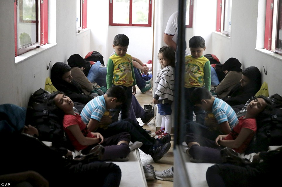 Crowded: Migrant children pile into a small room inside the former luxury hotel on the popular holiday resort of Kos