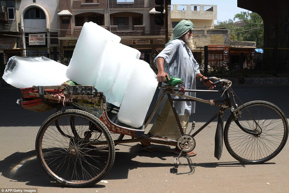 Cooling off: An Indian worker uses a rickshaw to transport huge blocks of ice from an ice factory in Amritsar as temperatures soar