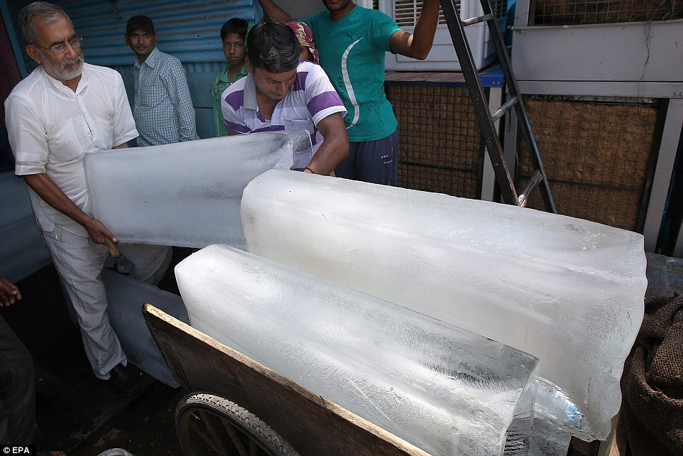 Indian workers load ice cubes up for sale as temperature rises in New Delhi. Andhra Pradesh state has been the worst hit with nearly 900 dying of heatstroke since May 18