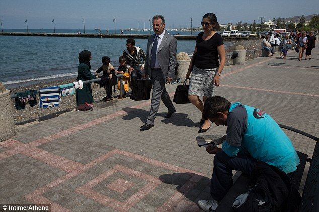 Out of place: A man in a suit and his smartly dressed companion walk past a family of migrants drying their clothes on the railing by the sea front at Kos