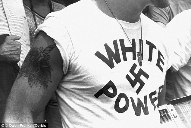 "In a picture from 1978, a man wears a pendant made out of a bullet and a t-shirt that reads ""White Power"" around a swastika at a gathering of American Naziis"