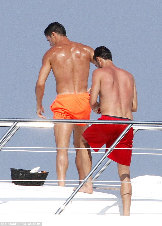 Helping hand: The 30-year-old star was spotted getting slathered in oil by his pal Miguel Paixão
