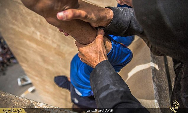 Gripped by his ankles, man is held above 100ft drop as bloodthirsty crowd wait to watch