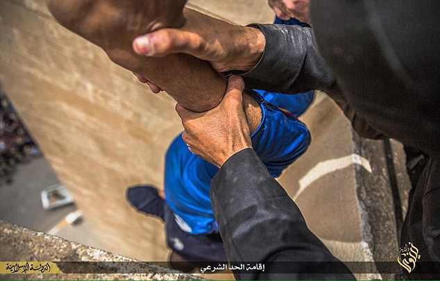 Sick: This disturbing photographs of the atrocity - believed to have been taken place in ISIS' stronghold Mosul - shows a gay man being dangled over the edge of the high building by his ankles before being dropped