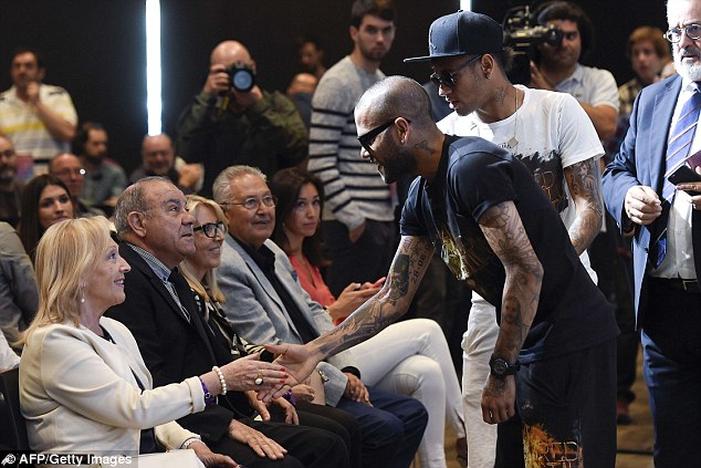 Alves, who is also set to leave Barcelona in the summer, shakes hands with Xavi's parents