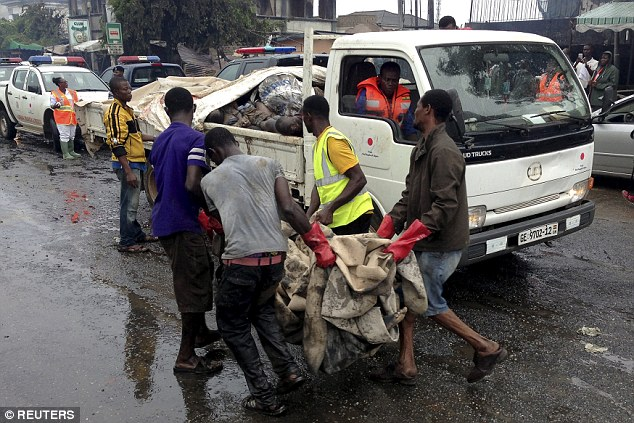 Sickening: Bodies are piled into the back of a pick-up truck. There are fears the death toll will continue to rise as more victims are found among the wreckage