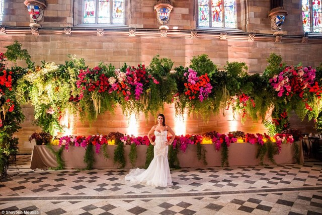 Above the bridal table hung a custom designed 12-metre truss structure positioned over the bridal table featuring cascading ferns, roses in oranges, pinks and reds and hydrangea accents