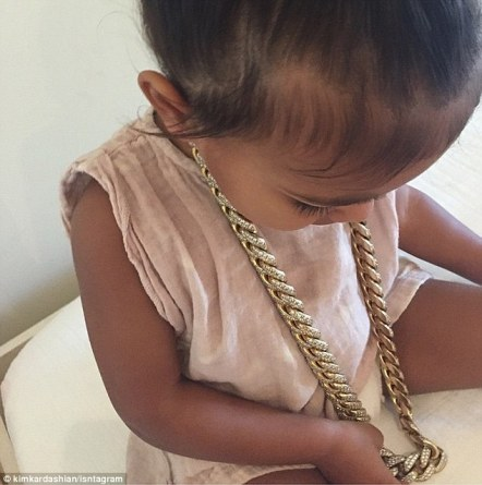 Already into jewelry: Kim Kardashian shared this image on Friday of daughter North wearing father Kanye West's yellow gold and diamond necklace. The 34-year-old captioned the image, 'No daddy it's me necklace'