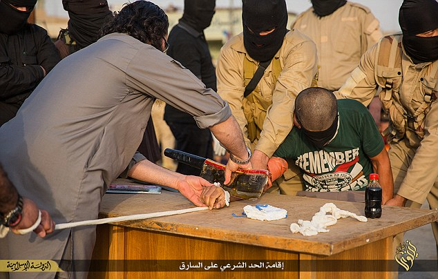 Braced for barbarity: A terrified Iraqi accused of being a thief is sentenced to have his hand chopped off with meat cleaver after being 'convicted' by an Islamic State court in the Iraqi province of Nineveh