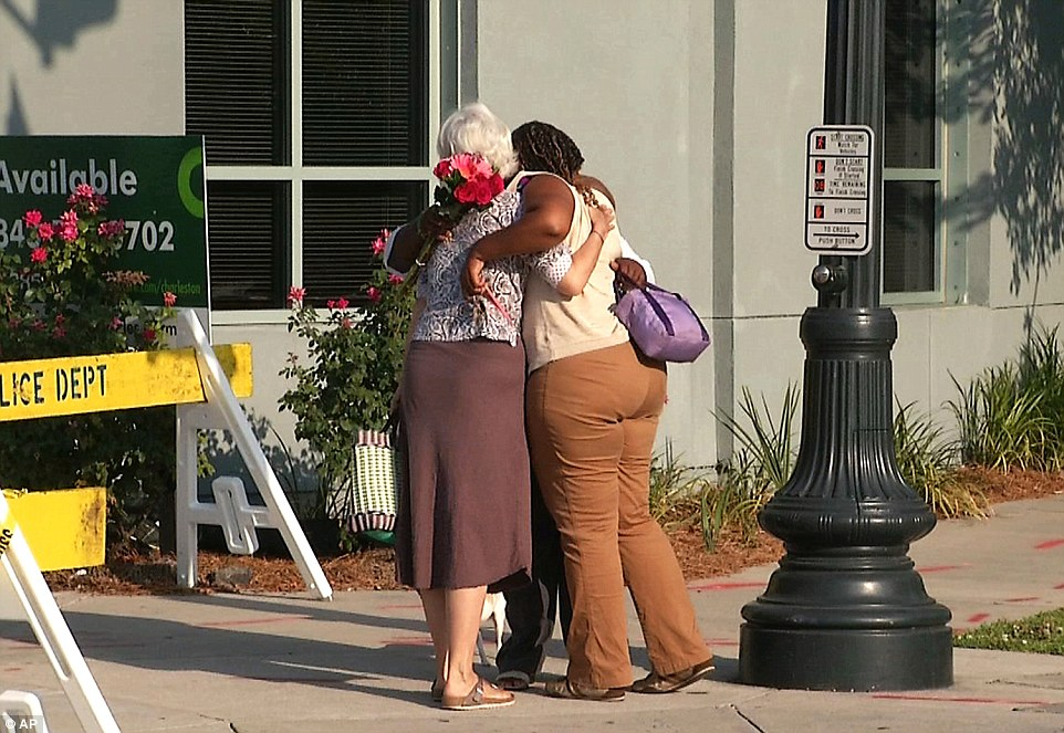 Heartbroken: Martha Watson, left, and Tarsha Moseley embrace at a makeshift memorial near Emanuel AME Church on Thursday