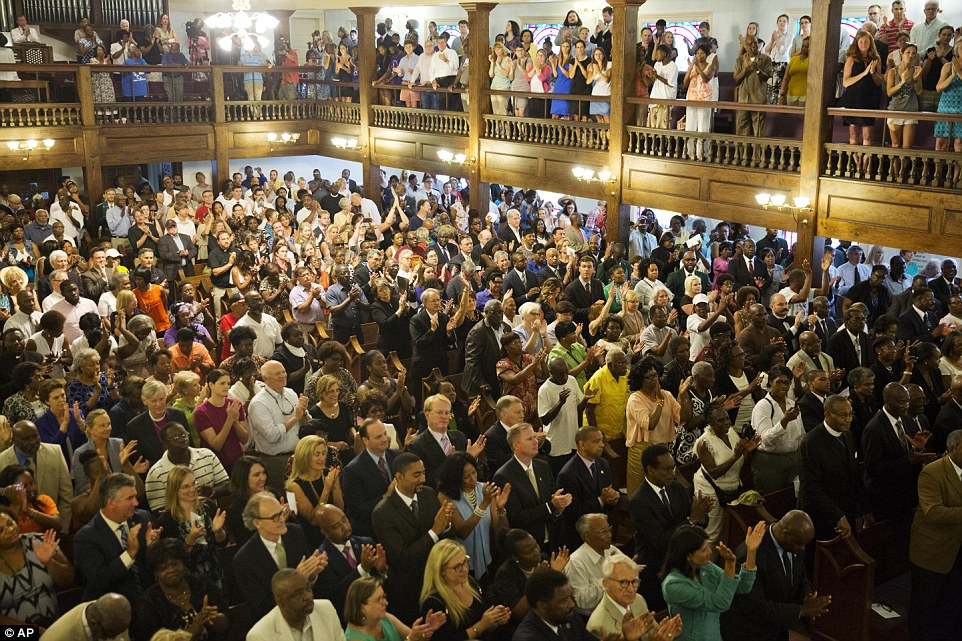 Services: Parishioners applaud during a memorial service at Morris Brown AME Church for the people killed on Wednesday