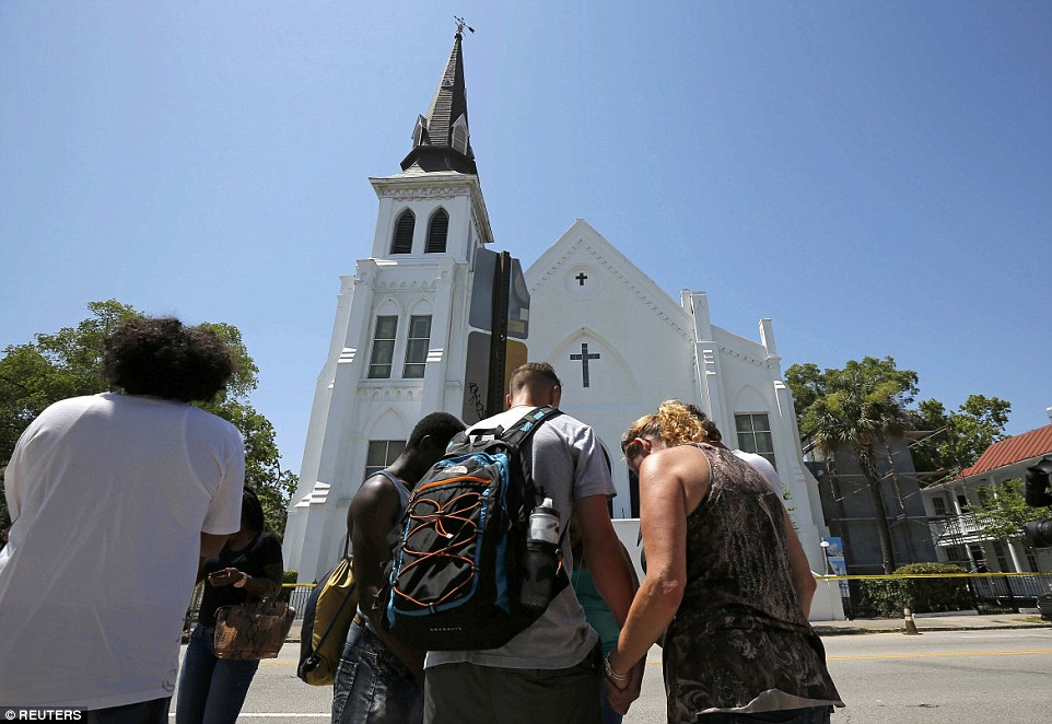 Prayers: Mourners pay their respects outside the church after the street was re-opened a day after the mass shooting