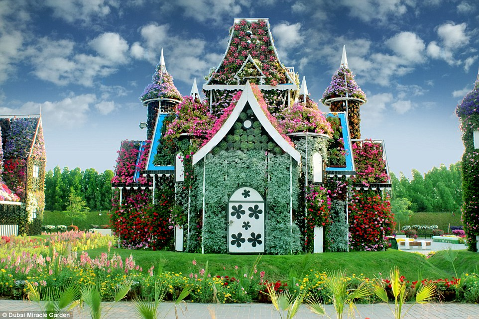 A fantasy flower house at the Miracle Garden, which has plants growing over its turrets, doors, walls and towers