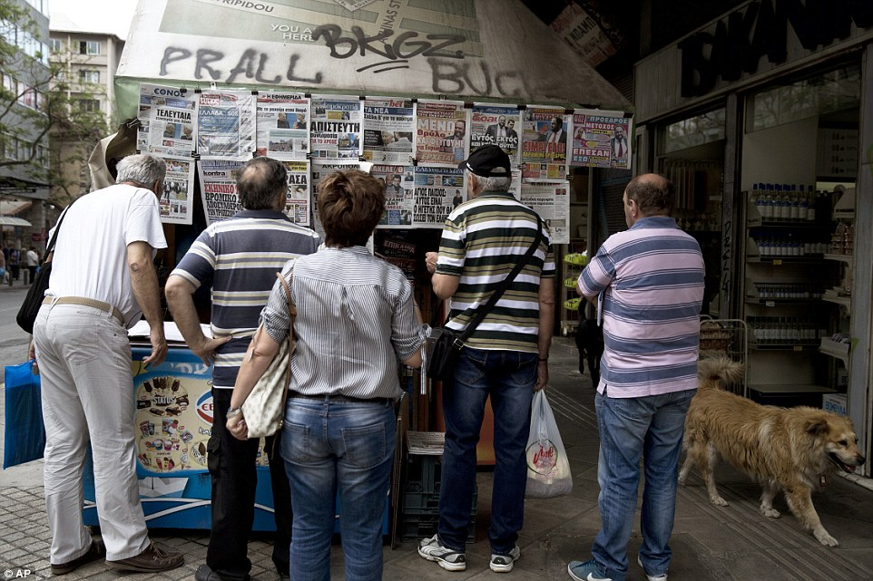 Stark: A stray dog passes by people looking at the newspapers reporting about Greece's bailout hanging at a kiosk in central Athens