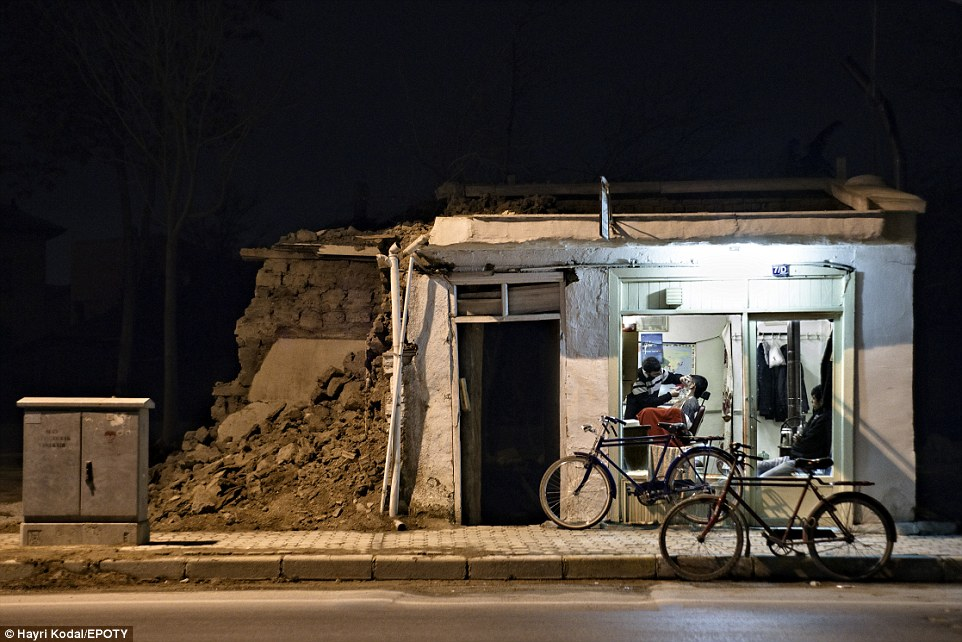 A lone barber shop stands in Konya, Turkey, with its electricity supply still working while all around it is crumbling and dark. Konya is best known as a busy university city and an economic boom town but this photograph tells a somewhat different story