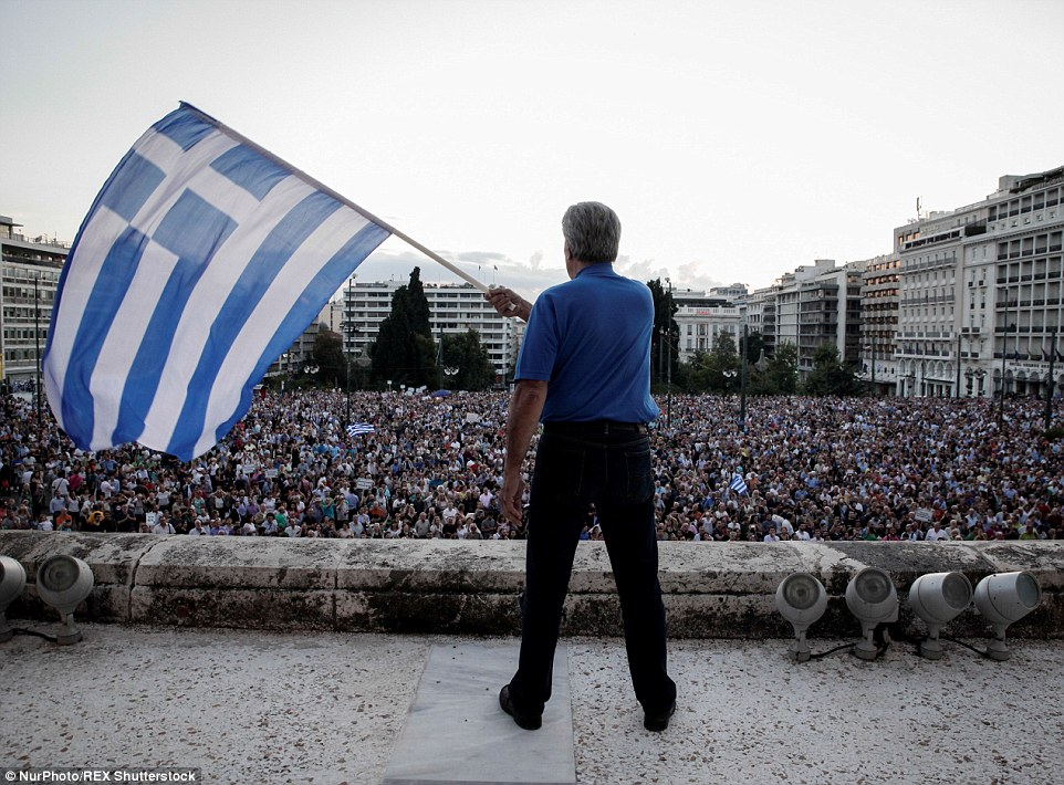 Crunch time: A protester waves a Greek flag in front of huge crowds at the entrance to the Greek Parliament building in Athens today
