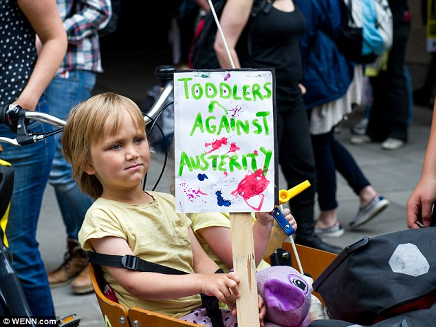 One child was seen bearing a placard saying 'toddlers against austerity' while being pushed along