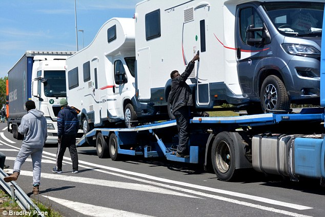 Chaos: Migrants attempting to climb in to caravans on the back of Lorries on the approach road to the Channel Tunnel during the strike  on Tuesday