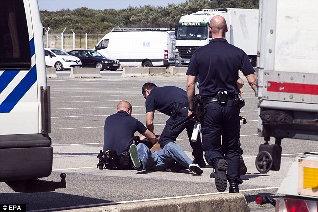 Violence: Police officers detain a migrant accused of throwing stones at a truck during a clash between migrants and a truck driver next of the ferry boat port of Calais on Wednesday