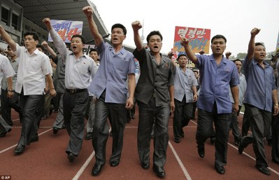 """Rally: Men pump their fists in the air and chant """"Defend!"""" as they carry propaganda slogans calling for reunification of their country during the """"Pyongyang Mass Rally on the Day of the Struggle Against the US"""