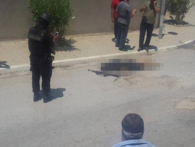 Police stand over one of the gunmen after the attack in the popular tourist destination today