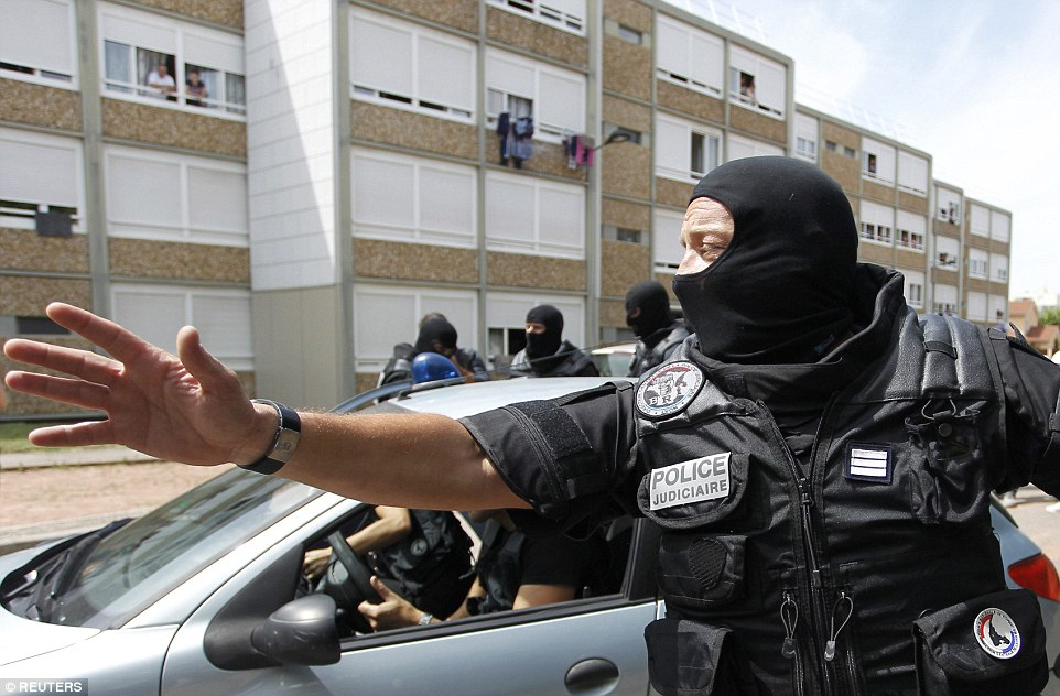 A French special  forces officer gestures as police escort a woman from a residential building during the raid in Saint-Priest