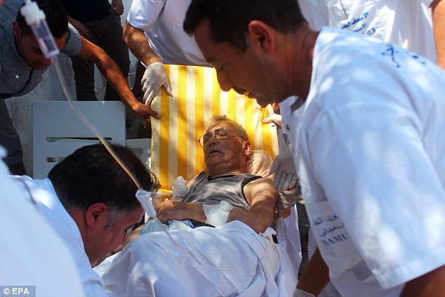 Medics help an injured man in Sousse after gunmen stormed beaches of two hotels in the town of Sousse
