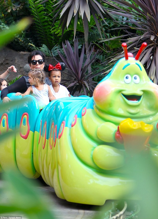 Just a big kid: Kris was having fun as she went on the rides with her grandchildren Penelope and North