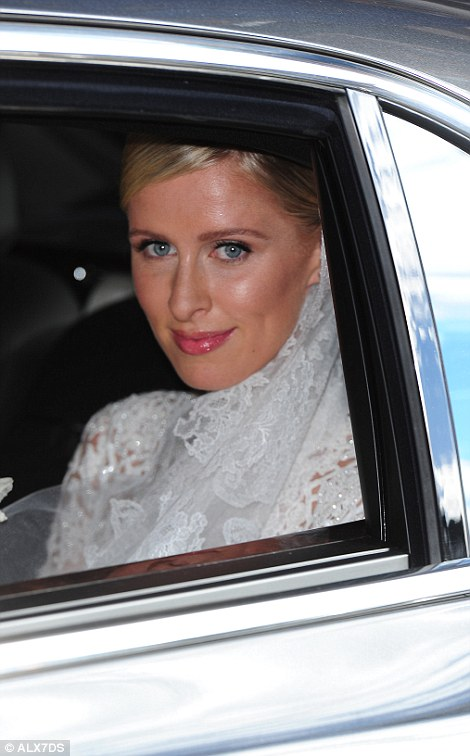 Here comes the bride: Miss Hilton sits in the back of her car as she is driven to her wedding at Kensington Palace