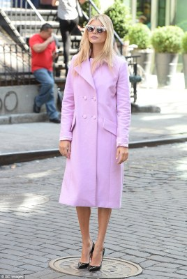 Demure: Later, Kelly swapped out of her kinky clobber in favour of a candy pink button up trench coat
