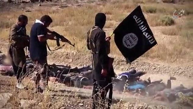 Los extremistas que sostiene la bandera y ametralladoras ISIS destacan sobre un grupo de prisioneros forzados a mentir en la tierra